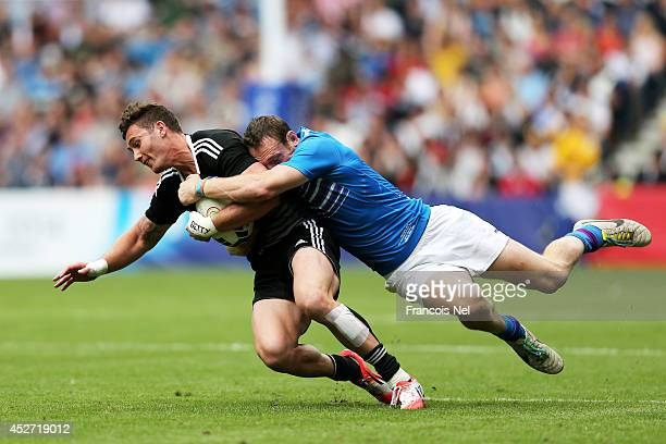 Gillies Kaka of New Zealand is tackled by Scott Riddell of Scotland in the Rugby Sevens match between New Zealand and Scotland at Ibrox Stadium...