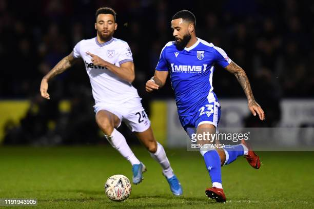 Gillingham's Scottish striker Alex Jakubiak runs with the ball chased by West Ham United's English defender Ryan Fredericks during the English FA Cup...