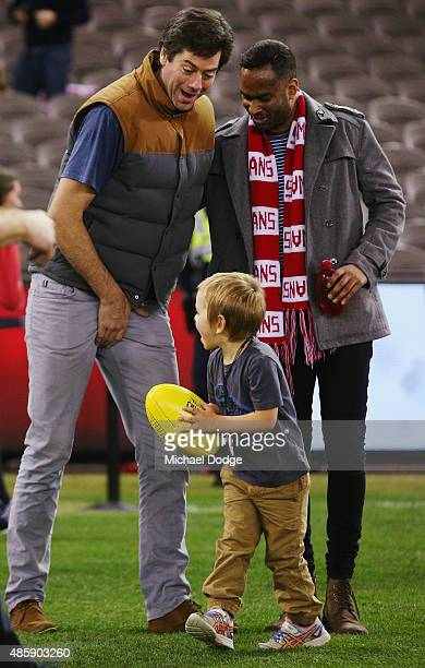 Gillon McLachlan reacts after getting hit in the groin by his son Sidney McLachlan while participating in kick to kick after the round 22 AFL match...