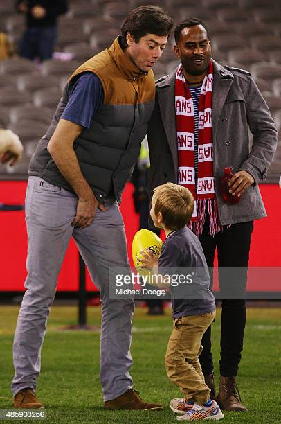 Gillon McLachlan reacts when getting hit in the groin by his son Sidney McLachlan while participating in kick to kick after the round 22 AFL match...