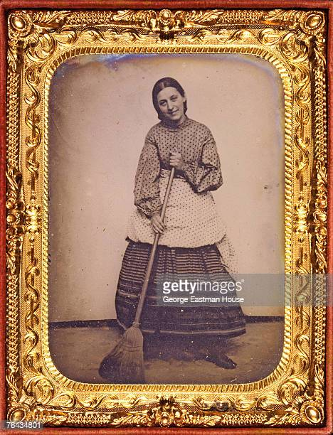 Giltframed tintype portrait of a woman in a polkadot blouse and arpon over a striped skirt who holds a broom mid 1860s