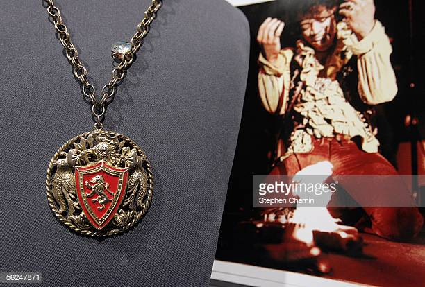 A giltmetal necklace and enamel medallion worn by Jimi Hendrix on stage at the Monterey Pop Festival in 1967 hangs on display next to a photo of him...