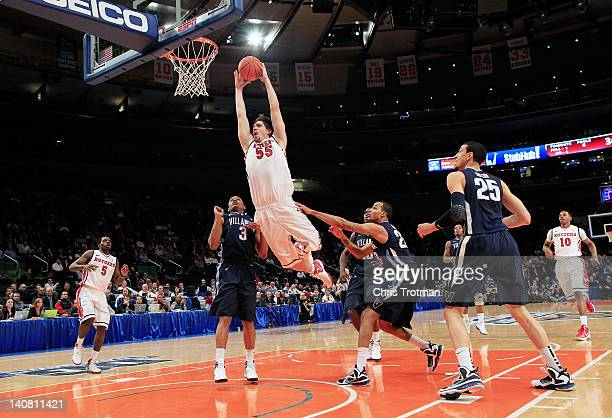 Gilvydas Biruta of the Rutgers Scarlet Knights leaps to the basket over Ty Johnson of the Villanova Wildcats during their first round game of the...