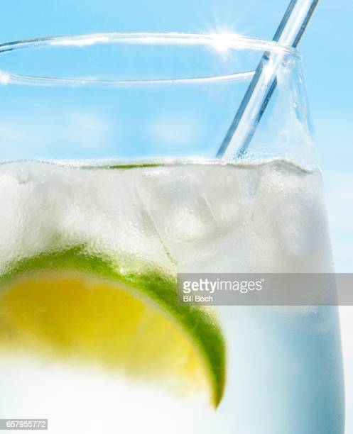 Gin and tonic water cocktail with lime wedge - outside closeup