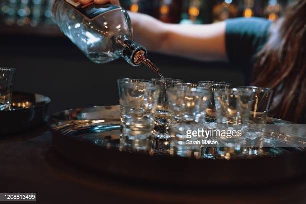 gin being poured into shot glasses - femalefocuscollection stock pictures, royalty-free photos & images