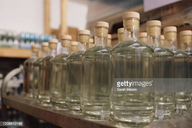 gin bottles with stoppers in production - femalefocuscollection stock pictures, royalty-free photos & images