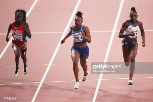 Gina Bass of Gambia Teahna Daniels of the United States and Daryll Neita of Great Britain compete in the Women's 100 Metres semifinal during day...