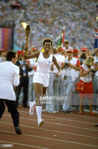 Jesse Owens' Granddaughter Gina Hemphill runs through the stadium with the Olympic Torch before the 1984 Olympic Games at the Coliseum Stadium in Los...