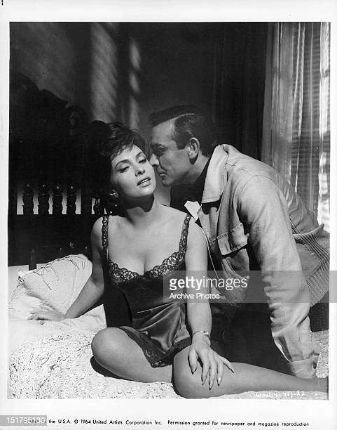 Gina Lollobrigida and Sean Connery sitting on a bed in a scene from the film 'Woman Of Straw' 1964