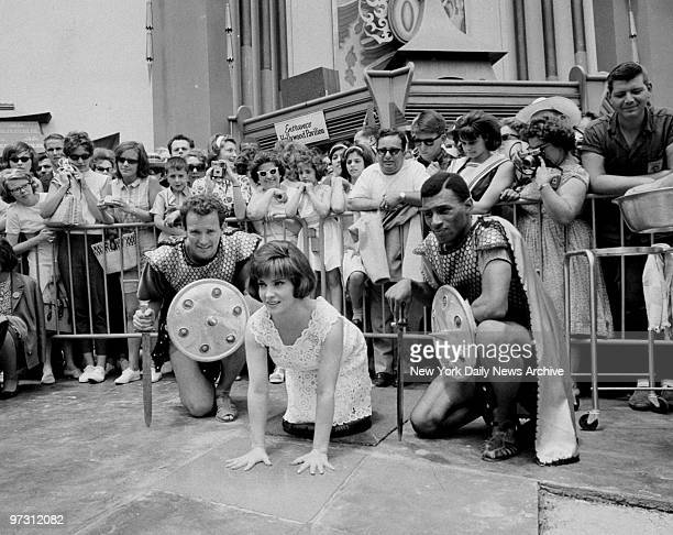 Gina Lollobrigida flanked by two Roman soldiers imprints hands in cement at Hollywood Pavilion in World's Fair