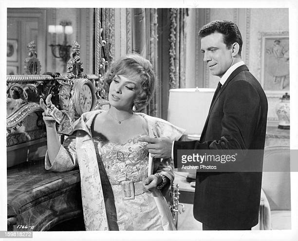 Gina Lollobrigida holding cash in front of Anthony Franciosa in a scene from the film 'Go Naked In The World' 1961