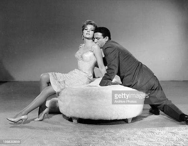 Gina Lollobrigida is adored by Anthony Franciosa in publicity portrait for the film 'Go Naked In The World' 1961