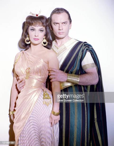 Gina Lollobrigida Italian actress and Yul Brynner US actor both in costume in a studio portrait against a white background issued as publicity for...