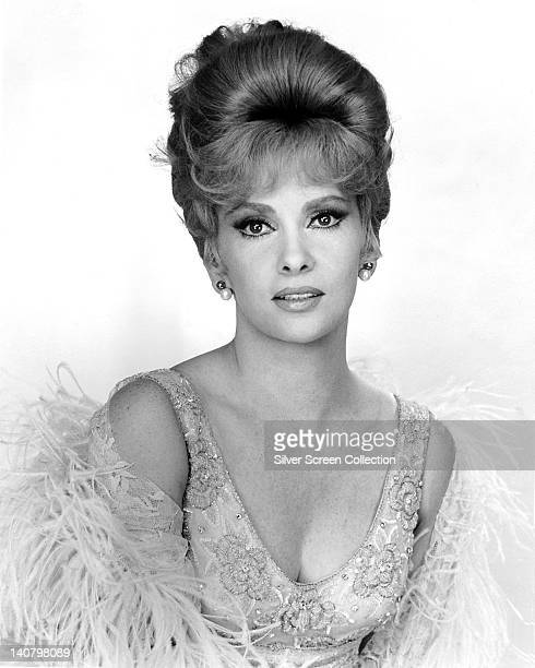 Gina Lollobrigida Italian actress wearing sequinned lowcut top wrapped in a feather boa in a studio portrait against a white background circa 1950