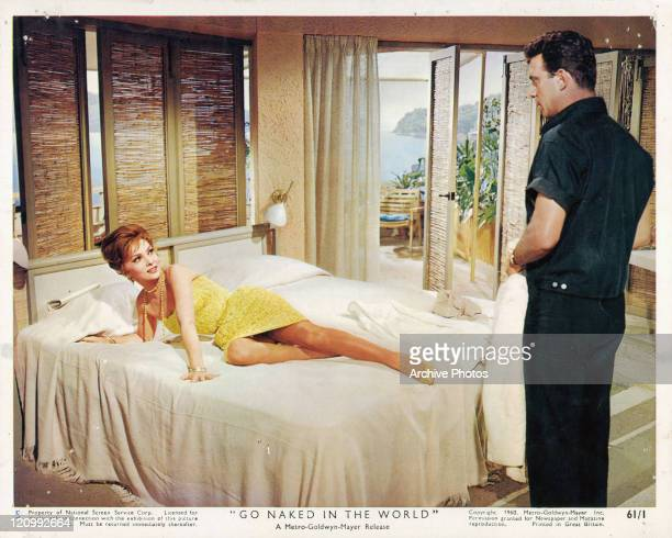 Gina Lollobrigida lye's on bed looking at Anthony Franciosa who's standing at the foot of the bed in a scene from the film 'Go Naked In The World'...
