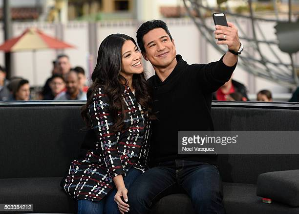 Gina Rodriguez takes a selfie with Mario Lopez at 'Extra' at Universal Studios Hollywood on January 4 2016 in Universal City California