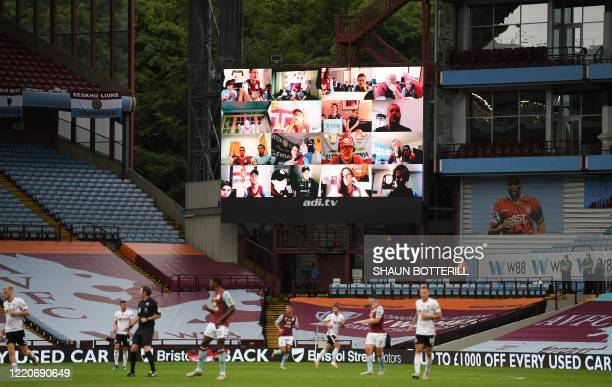 TOPSHOT A ginat screen shows images of Aston Villa fans as they watch the match from their computers during the English Premier League football match...