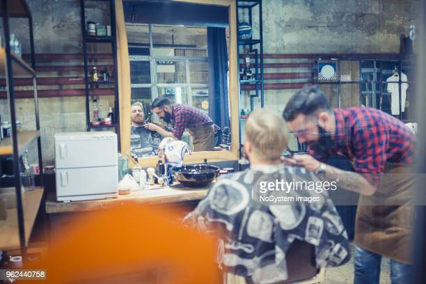 Gingembre, barbu gars à la boutique du coiffeur