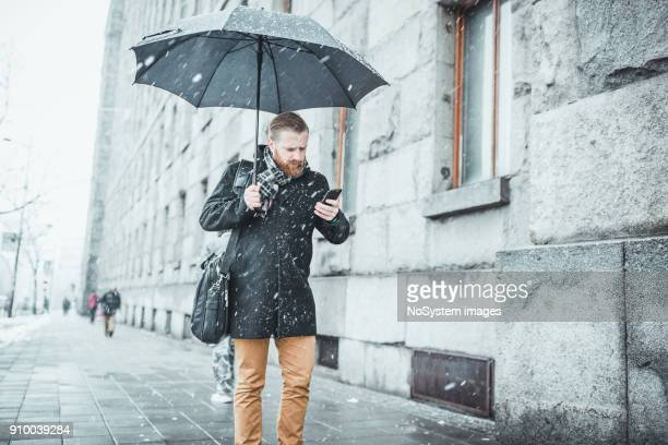 Ginger businessman walking in the snow, talking on mobile phone. Belgrade, Serbia, Europe