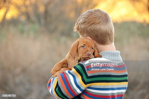 ginger hair boy and his vizsla puppy - ginger lynn stock-fotos und bilder