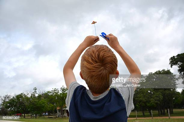 ginger hair boy flying a kite on a cloudy day - ginger lynn stock-fotos und bilder