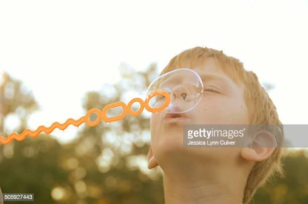 ginger haired boy blowing bubbles into the sky - ginger lynn stock-fotos und bilder