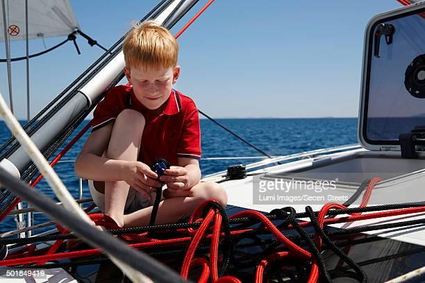Ginger haired boy playing on sailboat, Dalmatia, Croatia, Europe