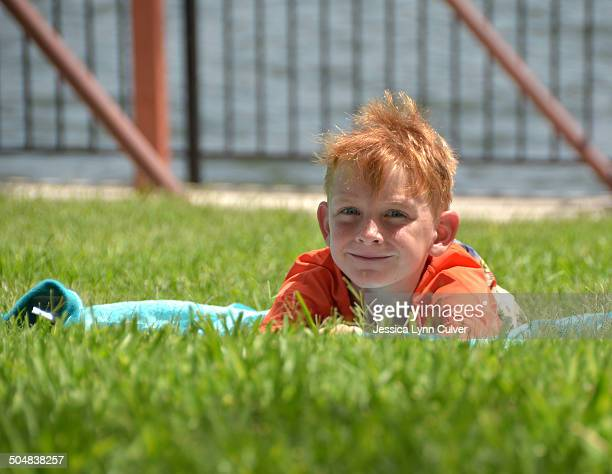 ginger haired boy relaxing on a towel by a lake - ginger lynn stock-fotos und bilder