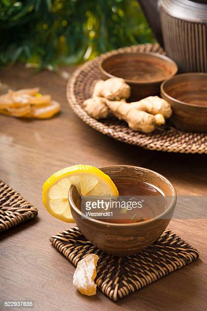 Ginger lemon tea in a tea bowl, candied and fresh ginger
