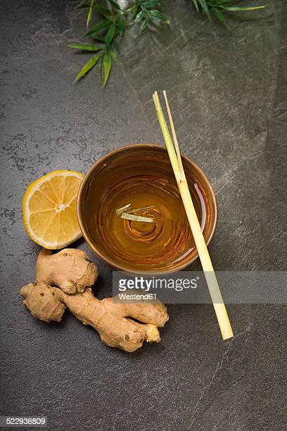 Ginger lemon tea in a tea bowl with fresh lemongrass and ginger