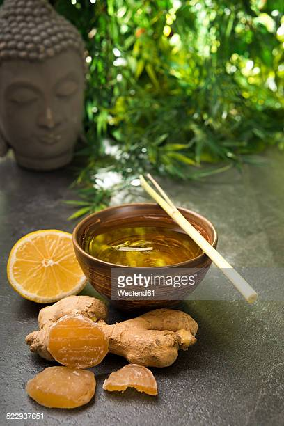 Ginger lemon tea in a tea bowl with fresh lemongrass, candied and fresh ginger