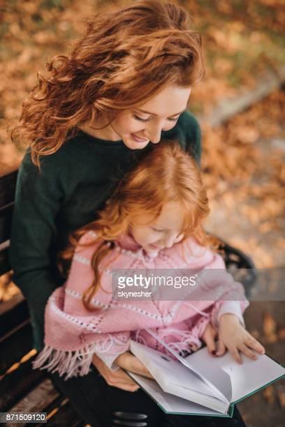 leer un libro a su hija en el parque de la madre de jengibre. - ginger lee fotografías e imágenes de stock