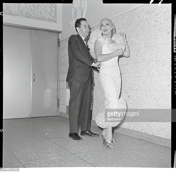 Ginger Rogers gets her Daiquiritoned French lace dress fitted by its designer Richard Meril in preparation for the Prestige Award from France fashion...