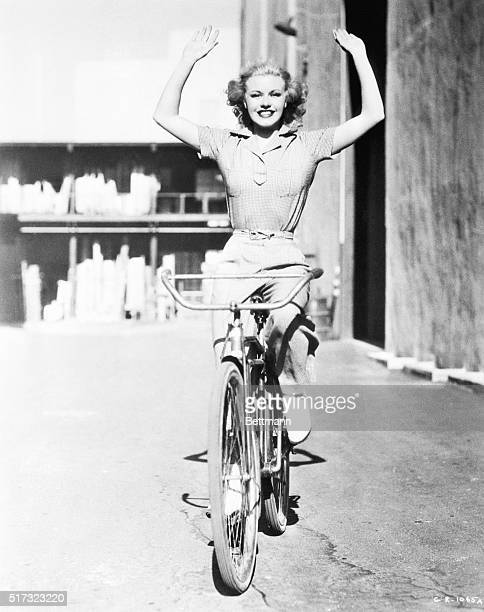 Ginger Rogers holds her hands up high while riding a bicycle on the RKO Radio Pictures lot on July 1 1936