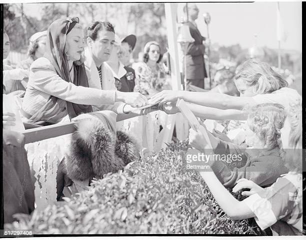 Ginger Rogers signing autographs for young admirers at the recent polo game held on the Will Rogers Memorial Field while her escort Pat Decicco...