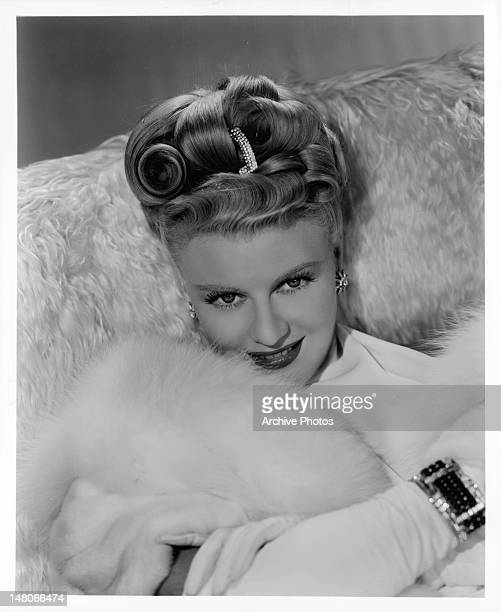 Ginger Rogers surrounded in white fur for a photograph in a scene from the film 'WeekEnd At The Waldorf' 1945