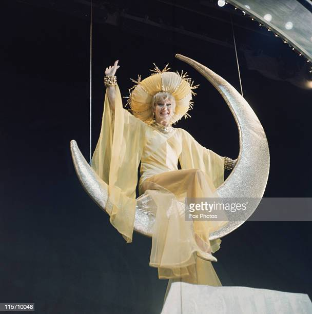 Ginger Rogers US actress and dancer in costume as she perches on a crescent moon suspended above the stage during a production of 'Mame' at the...