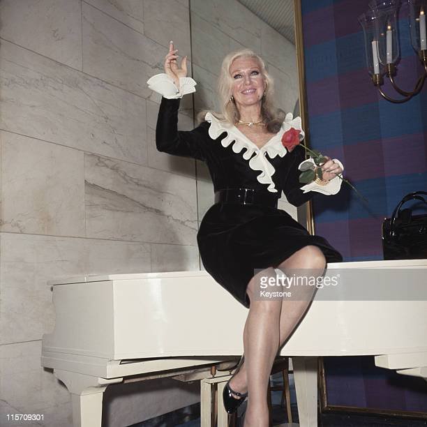 Ginger Rogers US actress and dancer wearing a black dress with white collar and cuffs while sittiing on top of a white grand piano while holding a...