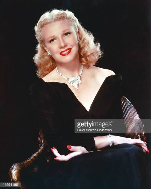 Ginger Rogers US actress and dancer wearing a lowcut Vneck outfit with an ornate silver necklace in a studio portrait against a black background...