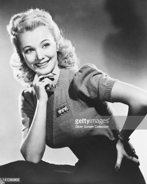 Ginger Rogers US actress and dancer wearing a shortsleeve knitted top posing with her chin resting on her right hand in a studio portrait circa 1945
