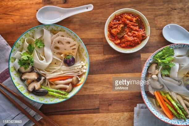 ginger shiitake lotus root soup with rice noodles - enoki mushroom stock pictures, royalty-free photos & images
