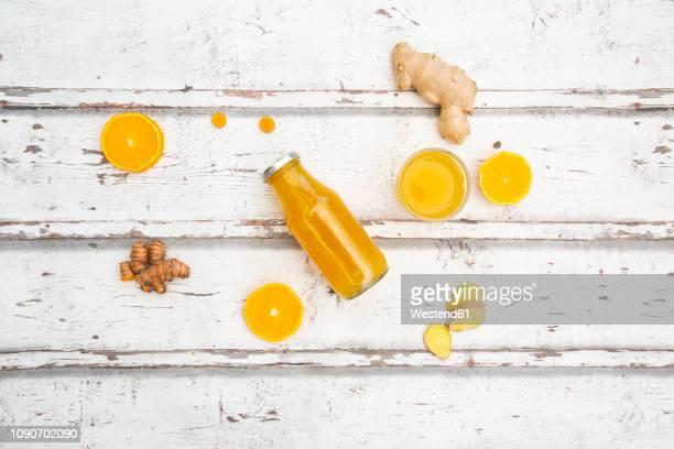 ginger shot with orange and curcuma on white wood - kaltes getränk stock-fotos und bilder
