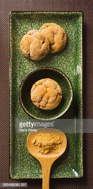 Ginger snap cookies and spoonful of ground ginger on serving tray