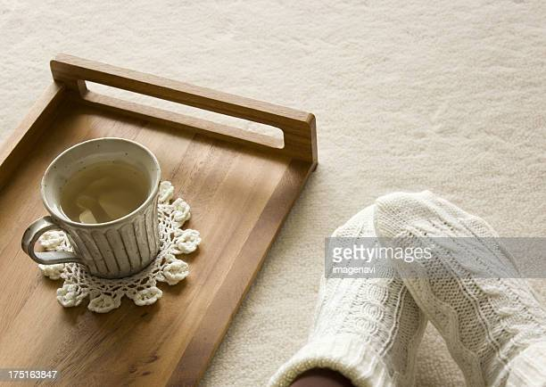 Ginger tea on a tray and feet wearing socks