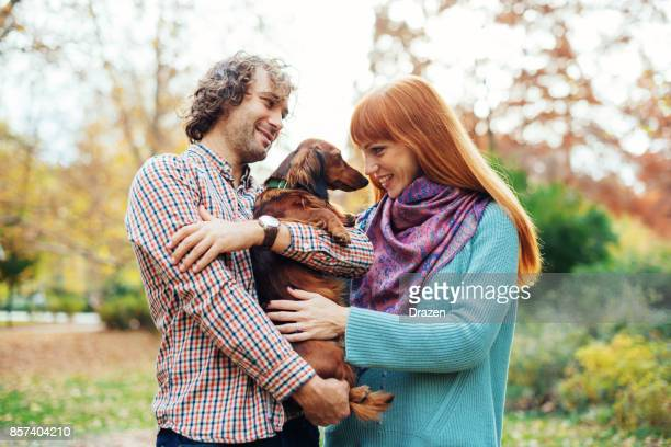 Ginger woman petting dachshund dog