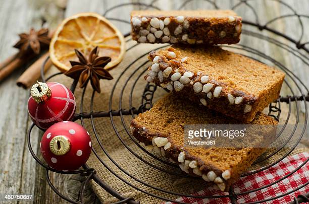 Gingerbread cake with christmas baubles and dried orange, spice on wooden table, close up