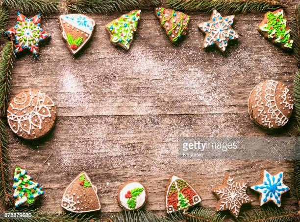 gingerbread christmas cookies pine branches frame on wooden table - country christmas stock pictures, royalty-free photos & images
