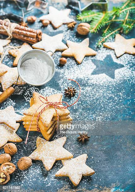 Gingerbread Christmas star shaped cookies with cinnamon, anise and nuts served with fir-tree branch on dark plywood background
