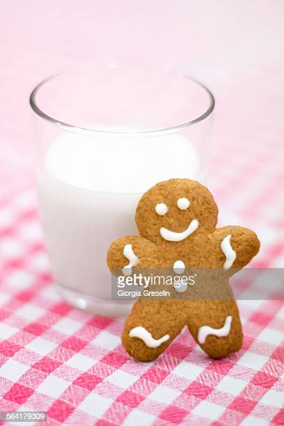 gingerbread cookie and a glass of milk - gingerbread man stock photos and pictures