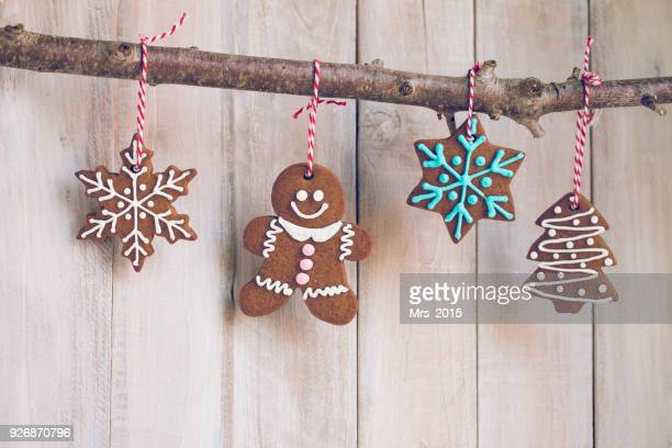 gingerbread cookies hanging on a branch - gingerbread man stock photos and pictures